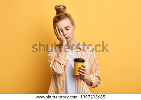 Tired sleepy woman holds a cup of coffee, has sad expression, closes eyes, cannot wake up in the morning and go to work. difficult, hard monday. isolated yellow background #1397203685