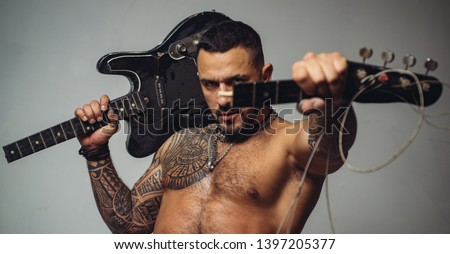 guitar player at rock concert. sexy abs of tattoo man hold broken electro guitar. sport and fitness. brutal sportsman torso. steroids. confidence charisma. muscular macho man with athletic body. #1397205377
