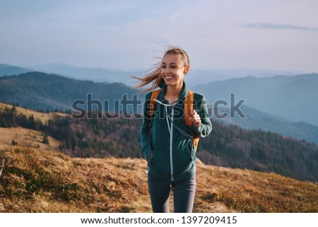 Portrait of a happy woman hiker standing on the slope of mountain ridge against mountains, blue cloudy sky on background. The woman is happy and looking at camera. Travel and active lifestyle concept. #1397209415