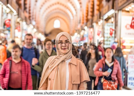 Portrait of beautiful Muslim woman in headscarf and fashionable modern clothes stands among people in grand Bazaar,Istanbul,Turkey.Modern Muslim women lifestyle business or travel tourist concept #1397216477