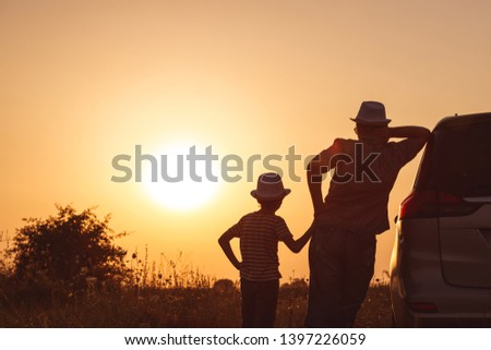 Father and son playing in the park at the sunset time. People having fun on the field. Concept of friendly family and of summer vacation. #1397226059
