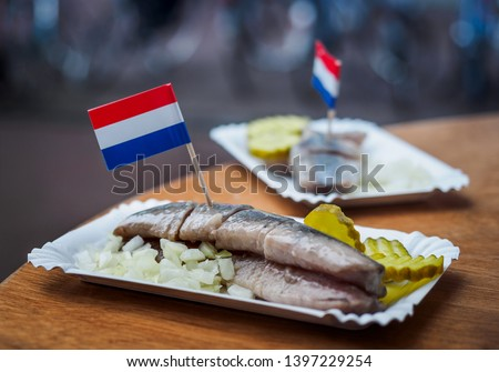 Traditional Dutch street food - saline herring with pickles, onions and Dutch flags in a fish. Still life with the Amsterdam snack in a soft focus. #1397229254