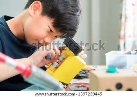 Closeup: Smart looking Asian boy working with circuits, wires, computer chip, OLED, motor, wheels on his robotics project. Science, Technology, Engineering and Mathematics (STEM) education concept. #1397230445
