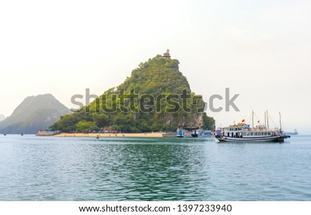 Beautiful Tourist cruise ship floating among limestone rocks at Ha Long Bay. This is the UNESCO World Heritage Site, it is a beautiful natural wonder in northern Vietnam Royalty-Free Stock Photo #1397233940