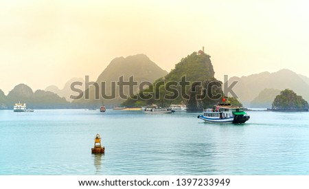 Beautiful Tourist cruise ship floating among limestone rocks at Ha Long Bay. This is the UNESCO World Heritage Site, it is a beautiful natural wonder in northern Vietnam Royalty-Free Stock Photo #1397233949