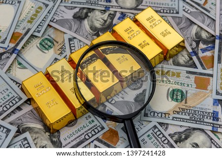 Bullion, gold or ingot on US dollar banknote with magnifier #1397241428