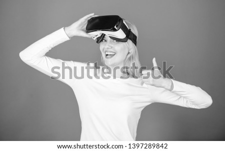 Amazed young woman touching the air during the VR experience. Woman watching virtual reality vision. Happy young woman wearing virtual reality goggles watching movies or playing video games #1397289842