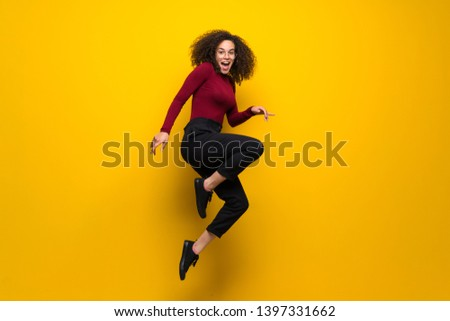 Dominican woman with curly hair jumping over isolated yellow wall #1397331662
