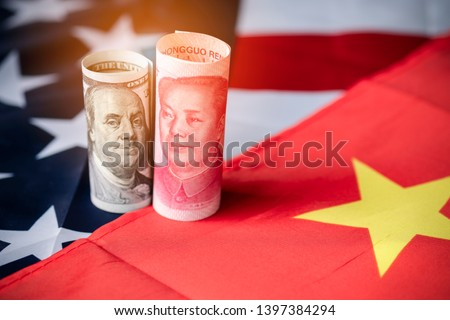US dollar and Yuan banknote on USA and China flags. Its is symbol for tariff trade war crisis between United States of America and China which the biggest economic country in the world. #1397384294