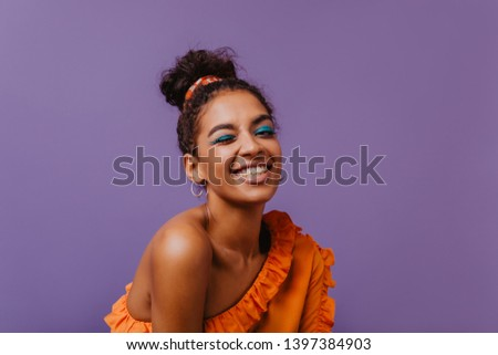 Good-humoured black girl funny smiling in studio. Ecstatic young woman in summer blouse chilling on purple background. #1397384903