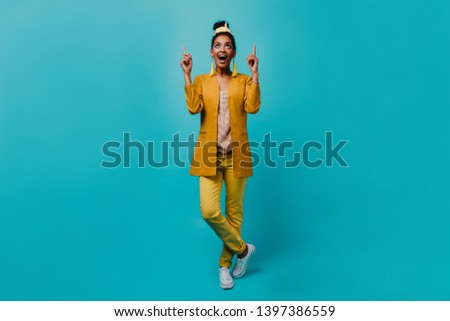 Indoor photo of refined black woman looking up. Studio shot of romantic girl wears yellow costume. #1397386559