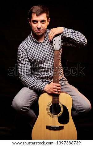 A guy playing an acoustic guitar. Fragment. Focus on the hand - #1397386739