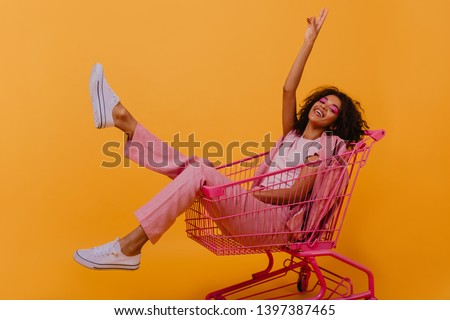 Refined african girl in pink costume having fun in studio. Relaxed young lady lying in shopping cart. #1397387465
