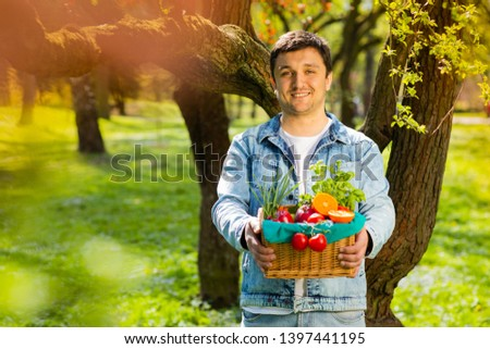 Basket with vegetables and fruits in the hands of a farmer background of nature. Concept of healthy lifestyle #1397441195