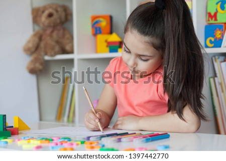 Happy cute child girl sitting at a table and drawing. Developmental activities. Back to school and happy time! #1397442770