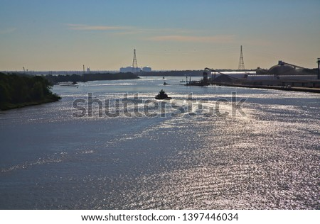 A tugboat heading down the Savannah River in the late afternoon lightg #1397446034