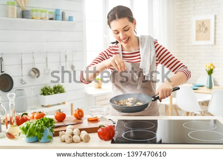 Healthy food at home. Happy woman is preparing the proper meal in the kitchen. #1397470610