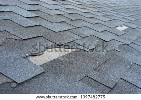 Close up view of asphalt shingles roof damage that needs repair. Royalty-Free Stock Photo #1397482775