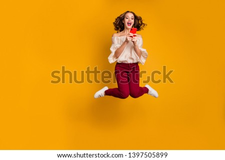 Full length body size view portrait of nice attractive slim fit thin glad cheerful cheery wavy-haired lady using modern technology device gadget isolated over bright vivid shine yellow background #1397505899