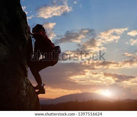 Young woman climbing high up on rock at sunset in mountains. Cloudy sky on background. Side view. Copy space for text. Difficult ascent to mountain top. Extreme, hiking, overcoming obstacles concept. #1397516624