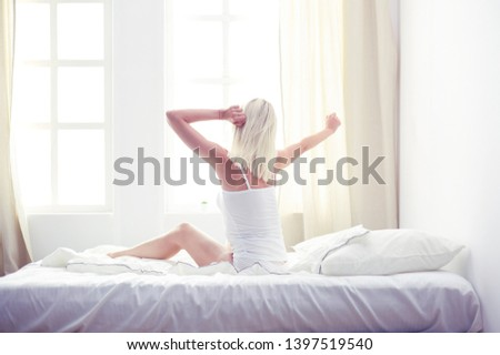 Woman stretching in bed after wake up, back view #1397519540