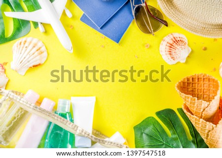 Travel and vacation flatlay concept. Summer bright colorful background with hat, sunglasses, plane,  passport, tropical leaves, travel cosmetics kit, seashells, copy space top view banner #1397547518