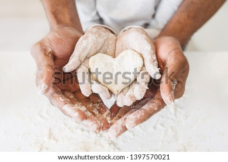 Afro man's hands holding childs hands with heart shaped pastry. Happy childhood concept #1397570021