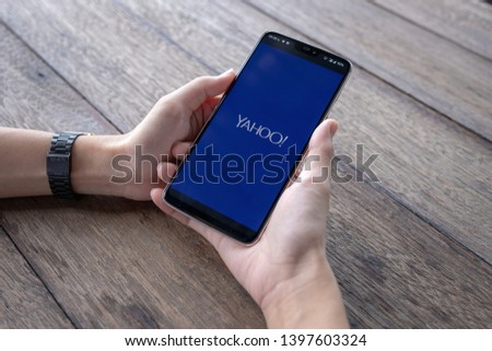Chiang Mai  Thailand - May 11 2019 : Hands hoding Oneplus 6 with yahoo screen, Coffee and keyboard on wood desk #1397603324