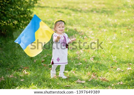 Child carries fluttering blue and yellow flag of Ukraine in field. Ukraine's Independence Day. Flag Day. Constitution day. Girl in traditional embroidery with flag of Ukraine #1397649389
