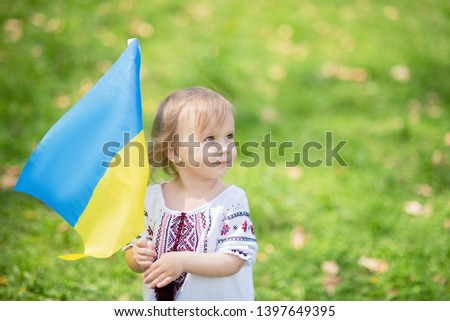 Child carries fluttering blue and yellow flag of Ukraine in field. Ukraine's Independence Day. Flag Day. Constitution day. Girl in traditional embroidery with flag of Ukraine #1397649395