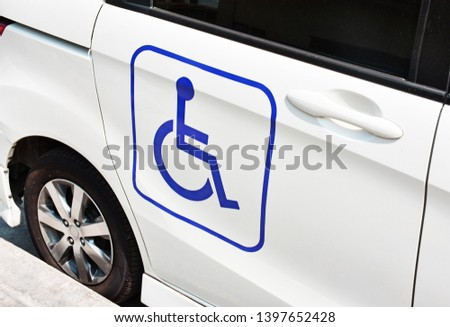 A handicap sign on the side of the white car. Handicapped people in car.