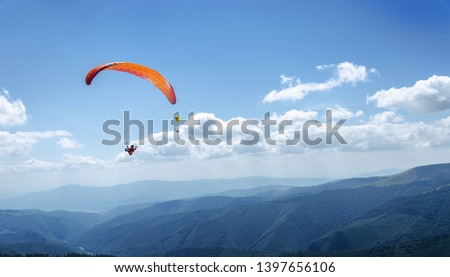 Paraglider in the blue sky. The sportsman flying on a paraglider. #1397656106