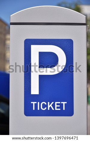 Blue parking sign with a big P and inscription ticket. Blue and white metal parking ticket dispensing sign. Automatic dispensing machine for park tickets. Sign of parking tickets on a city street #1397696471