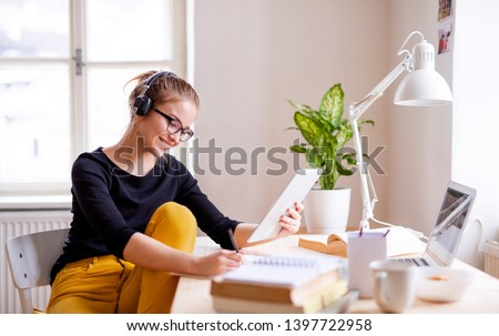 A young female student sitting at the table, using tablet when studying. Royalty-Free Stock Photo #1397722958