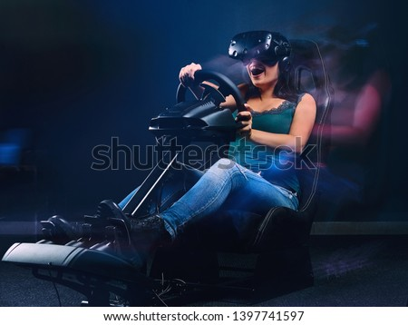 Woman wearing VR headset having fun while driving on car racing simulator cockpit with seat and wheel. #1397741597