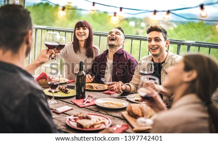 Young friends having fun drinking red wine at balcony penthouse dinner party - Happy people eating bbq food at fancy alternative restaurant together - Dinning lifestyle concept on warm vintage filter #1397742401