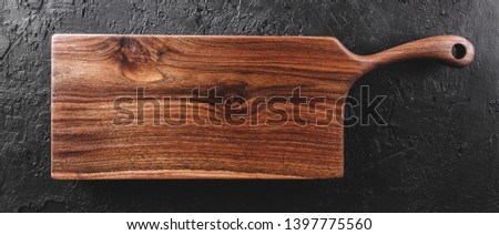 Chopping cutting board on dark stone background. Wooden texture. Top view, toning #1397775560