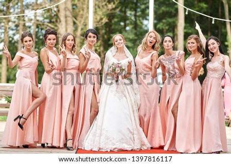 Wedding day. Beautiful bride and bridesmaids posing on the park on the wedding day. Bridesmaids dresses. Portrait of the bride and bridesmaids.  wedding day after wedding ceremony #1397816117