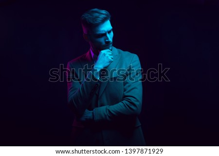 Young handsome model posing in a studio in a trendy neon light. Fashionable man in a stylish suit. Vibrant color. Bright colorful light effects. Disco style. Overlay. Gel filter. Supersaturated #1397871929