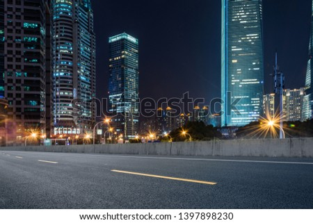 empty pavement and modern buildings in city in night #1397898230