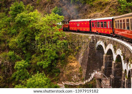 View from moving train on arch bridge over mountain slopes, beautiful view, one side mountain, one side valley. Toy train from Shimla to Kalka in Himachal Pradesh, India #1397919182