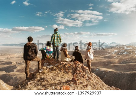 Group of tourists or friends stands at viewpoint and looks at mountains #1397929937