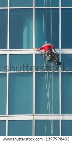 Climber - window cleaner perform the work at wall of an office building #1397998403