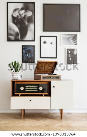 White wooden dresser with vintage radio and old gramophone. Gallery of prints on the wall. Real photo concept
