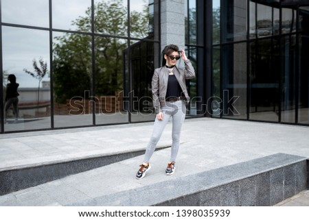 Street style photosession. Beautiful asian girl standing near modern house. Not looking in camera. Looking forward. #1398035939
