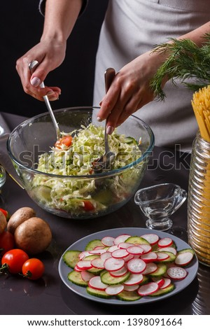 a young woman in a gray apron mixes a salad of Chinese cabbage #1398091664