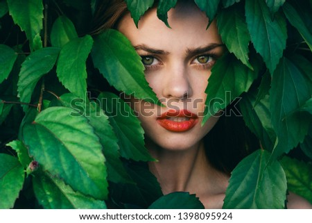Beautiful female face with bright makeup and green leaves around              #1398095924