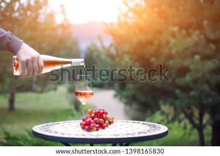 Man pouring rose wine to the glass in autumn vineyard on marble table. Harvest time, picnic or wine fest theme  #1398165830