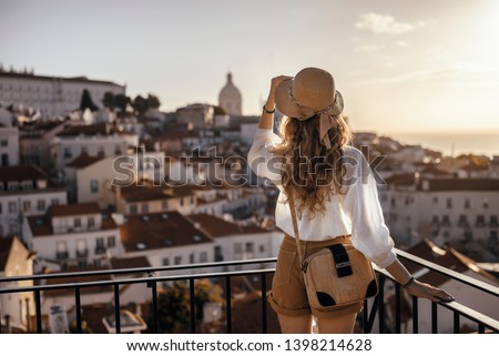 Blonde woman standing on the balcony and looking at coast view of the southern european city with sea during the sunset, wearing hat, cork bag, safari shorts and white shirt #1398214628