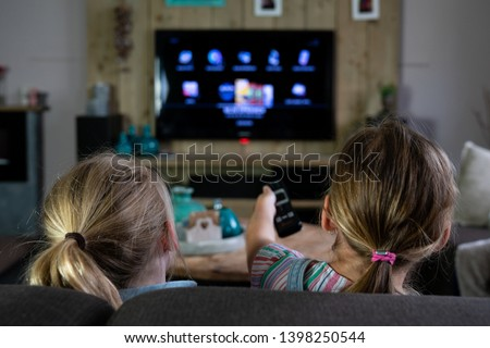 two children sliding through the apps on a smart tv. back of the children with the focus on the children #1398250544